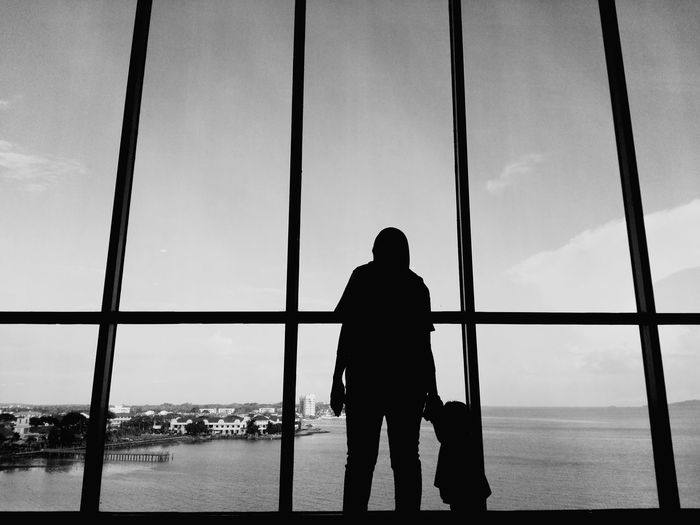 Silhouette mother with daughter standing by window against sea