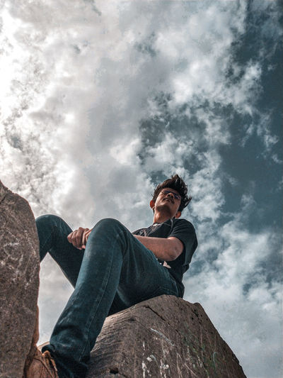 Low angle view of man sitting on rock against sky