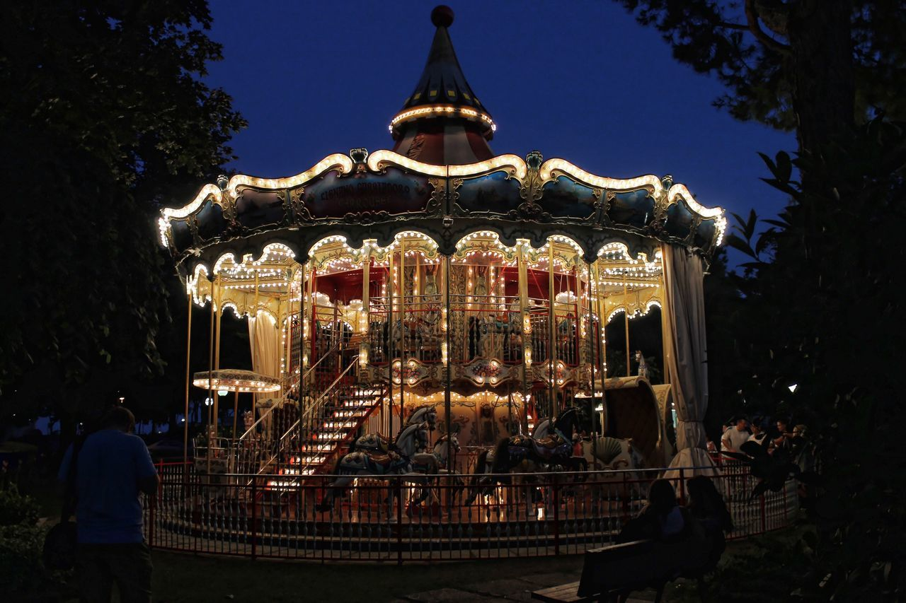 amusement park, carousel, arts culture and entertainment, amusement park ride, illuminated, leisure activity, night, enjoyment, outdoors, carousel horses, real people, merry-go-round, clear sky, sky