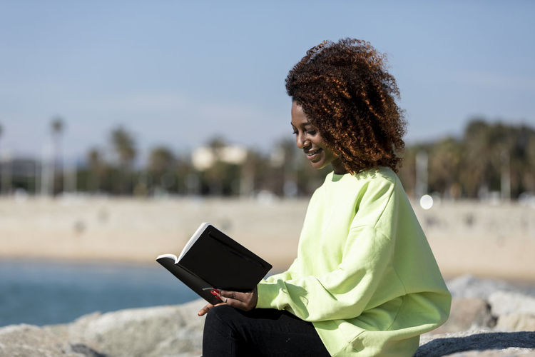 Side view of smiling woman with curly hair reading book while sitting at beach