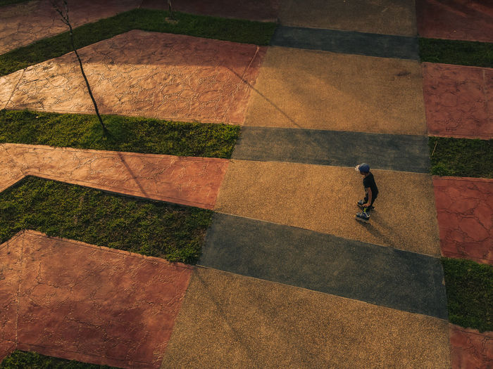 Shadow of boy playing rollerblade with nice pattern shot from above by drone