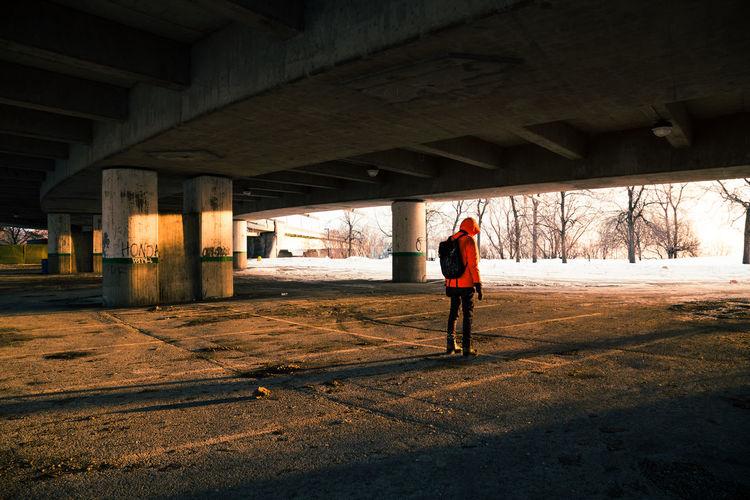 Rear view of man standing under bridge