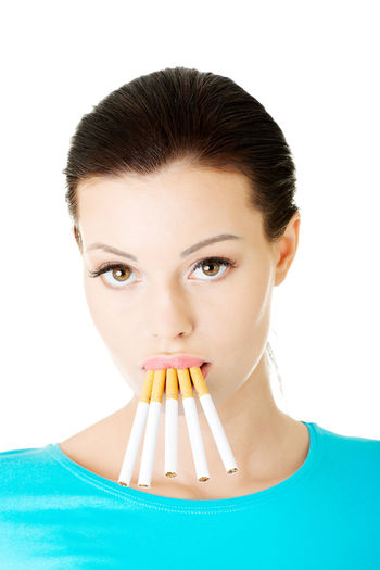 Close-Up Of Young Woman Smoking Cigarettes Standing Over White Background