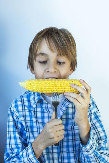 Teenager boy eating boiled corn cob. In a plaid shirt Teenager Boy Eating Boiled Corn Cob. In A Plaid Shirt