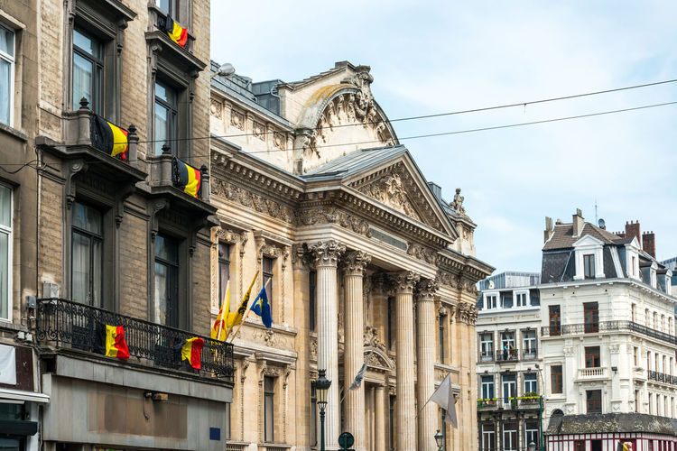 Low angle view of belgian flags on building in city against sky