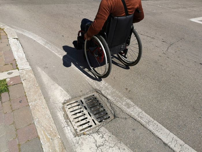 wheelchair in the streets of the city Real People Low Section Mode Of Transportation Medical Equipment Wheelchair Men Road Physical Impairment Outdoors Differing Abilities Street City One Person