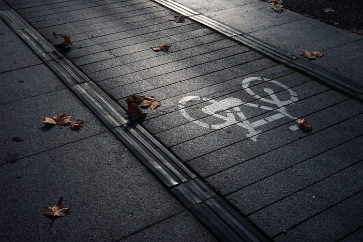 Bicyle sign Street Sign High Angle View Road Footpath No People Shadow Shades of Winter Outdoors Bicycle Day City