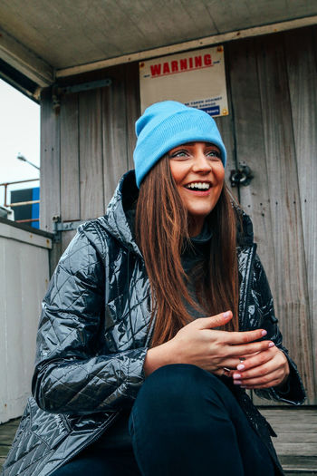 Smiling young woman wearing warm clothing while sitting outdoors