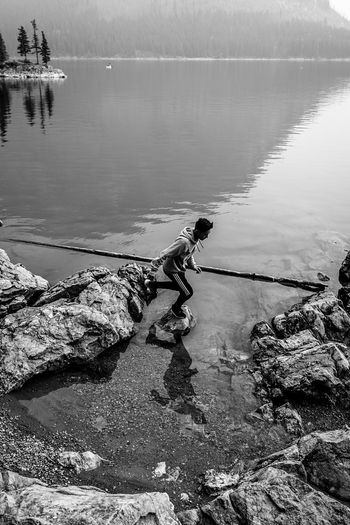 jumping over rocks Blackandwhite Monochrome Country Mountains person Lake Water Lake Reflection Sky Lakeshore