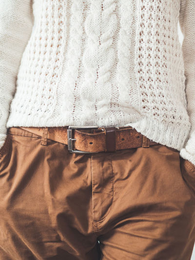 Woman in cable-knit sweater with pattern and brown chinos trousers with leather belt.casual clothes.
