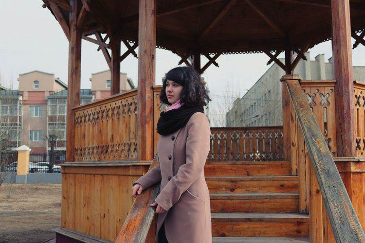 Side View Of Young Woman In Warm Clothing Looking Away While Standing On Steps