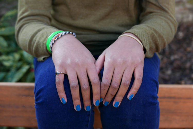 Midsection of woman with blue nail polish sitting on bench