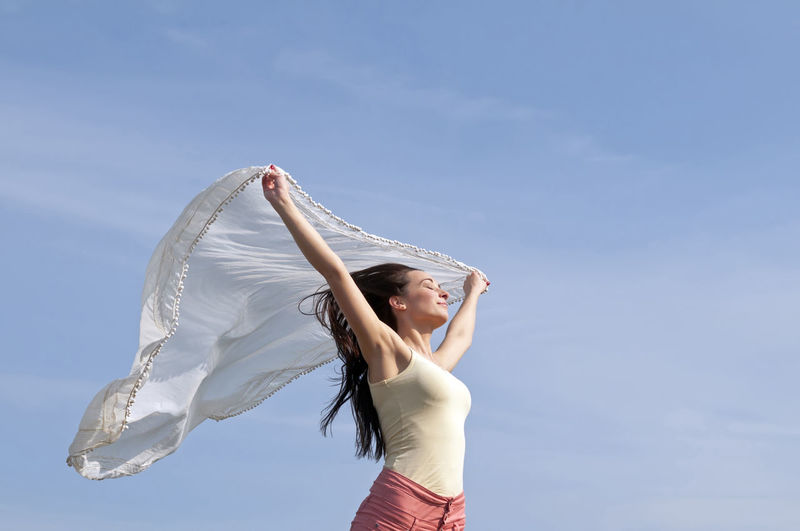 Low angle view of beautiful woman holding scarf against blue sky