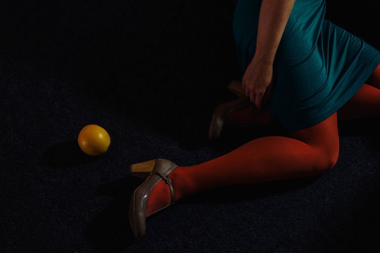 Low section of woman by orange on floor