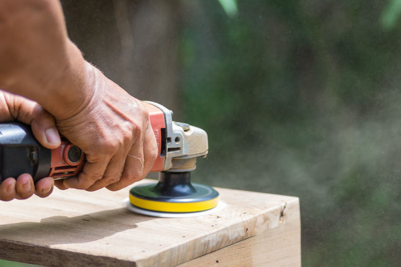 Cropped hands of person using work tool on wood