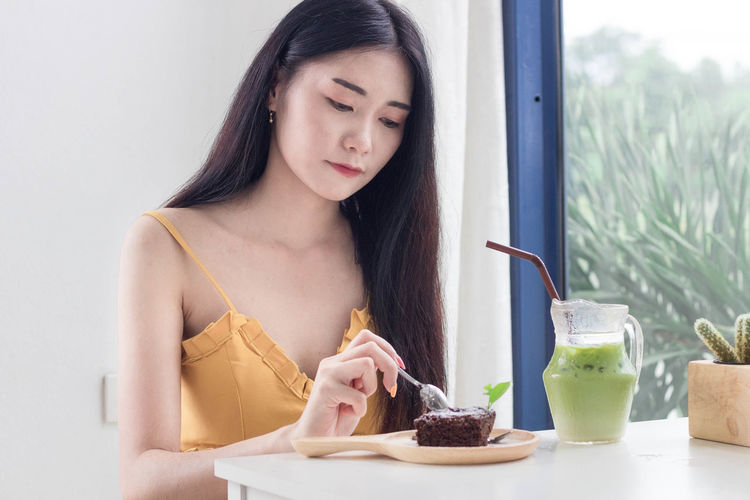 Young woman holding ice cream in glass on table