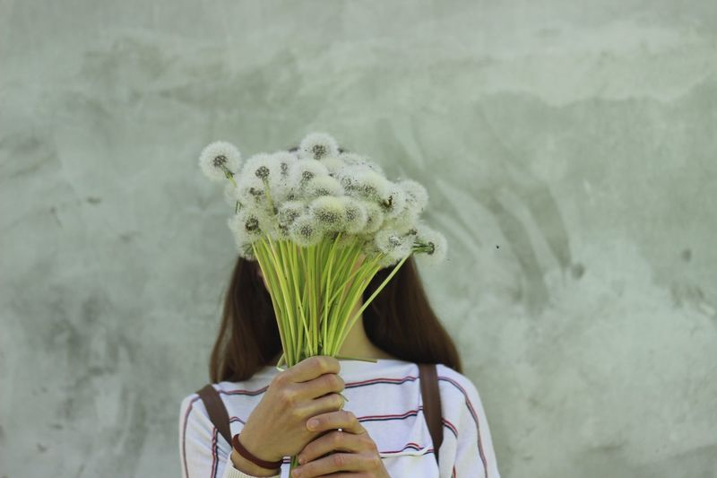 Mid Adult Woman Holding Flowers While Standing Against Wall