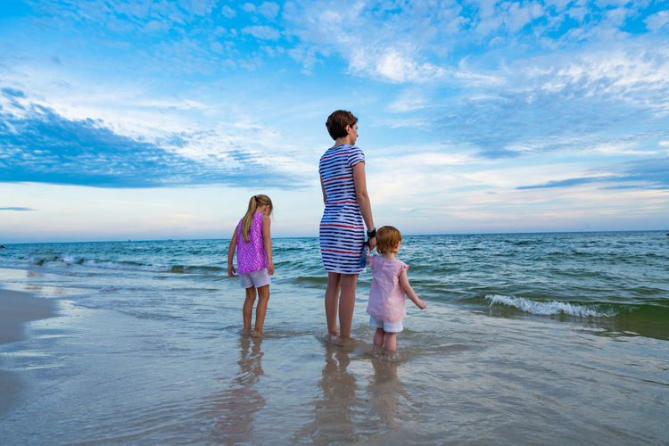 Introduction to the Ocean Beach Bonding Childhood Cloud - Sky Daughter Day Family Full Length Girls Horizon Over Water Leisure Activity Love Nature One Parent Real People Sand Sea Sky Standing Togetherness Vacations Water