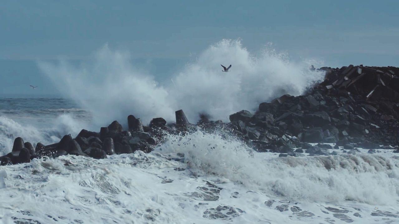Panoramic Shot Of Waves Breaking Against Sea