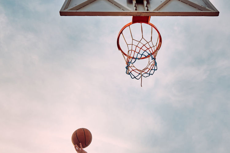 Hand of man throwing basketball to the basket hoop. bottom up view of basketball hoop and ball