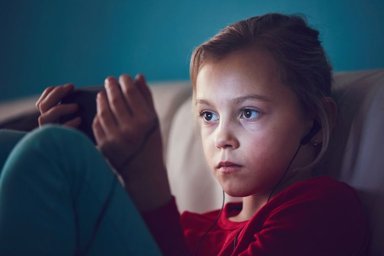 Close-Up Of Girl With Headphones Using Mobile Phone While Sitting On Sofa At Home