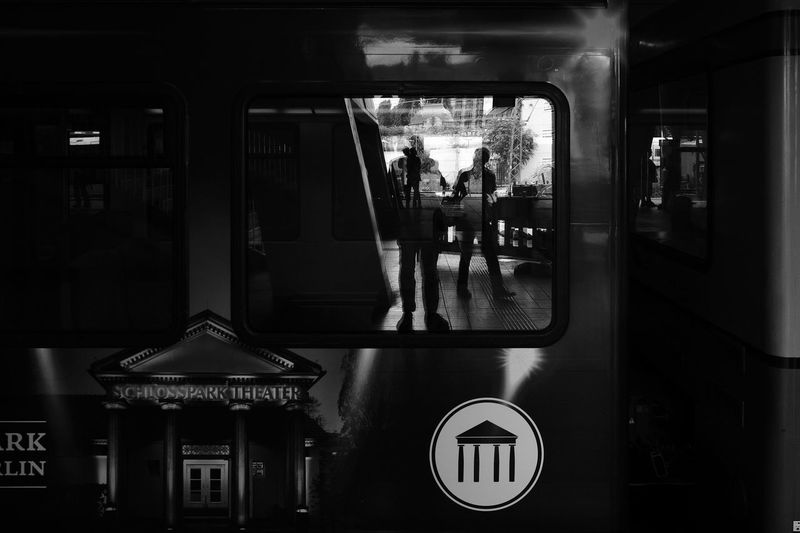 People at railroad station platform seen through train window