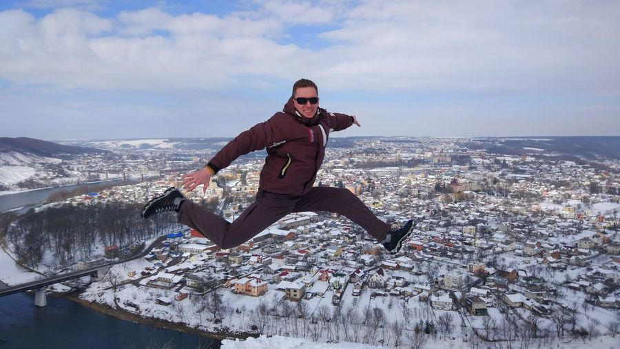 Full length of man jumping on snow against cityscape and sky