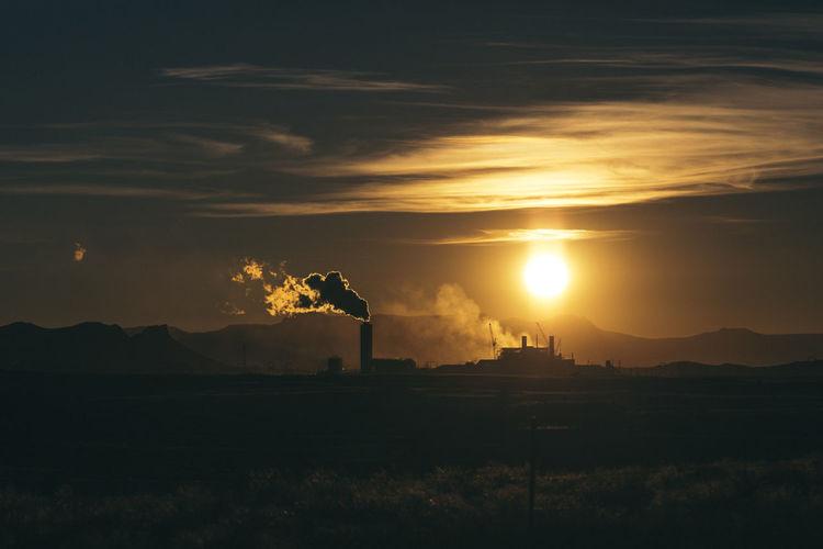 Smoke emitting from smoke stack against sky during sunset