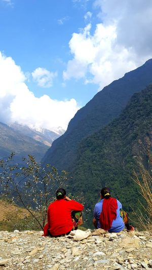 Rear view of people sitting on mountain against sky