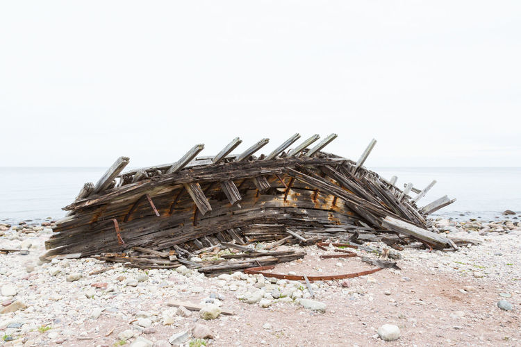Abandoned wooden structure on beach against clear sky