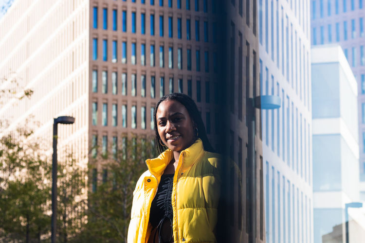 Portrait of smiling woman standing against building in city