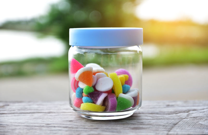 Close-up of colorful candies in jar on table
