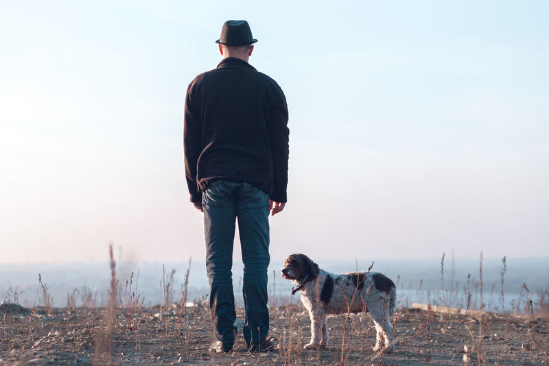 Rear view of man with dog on field against sky