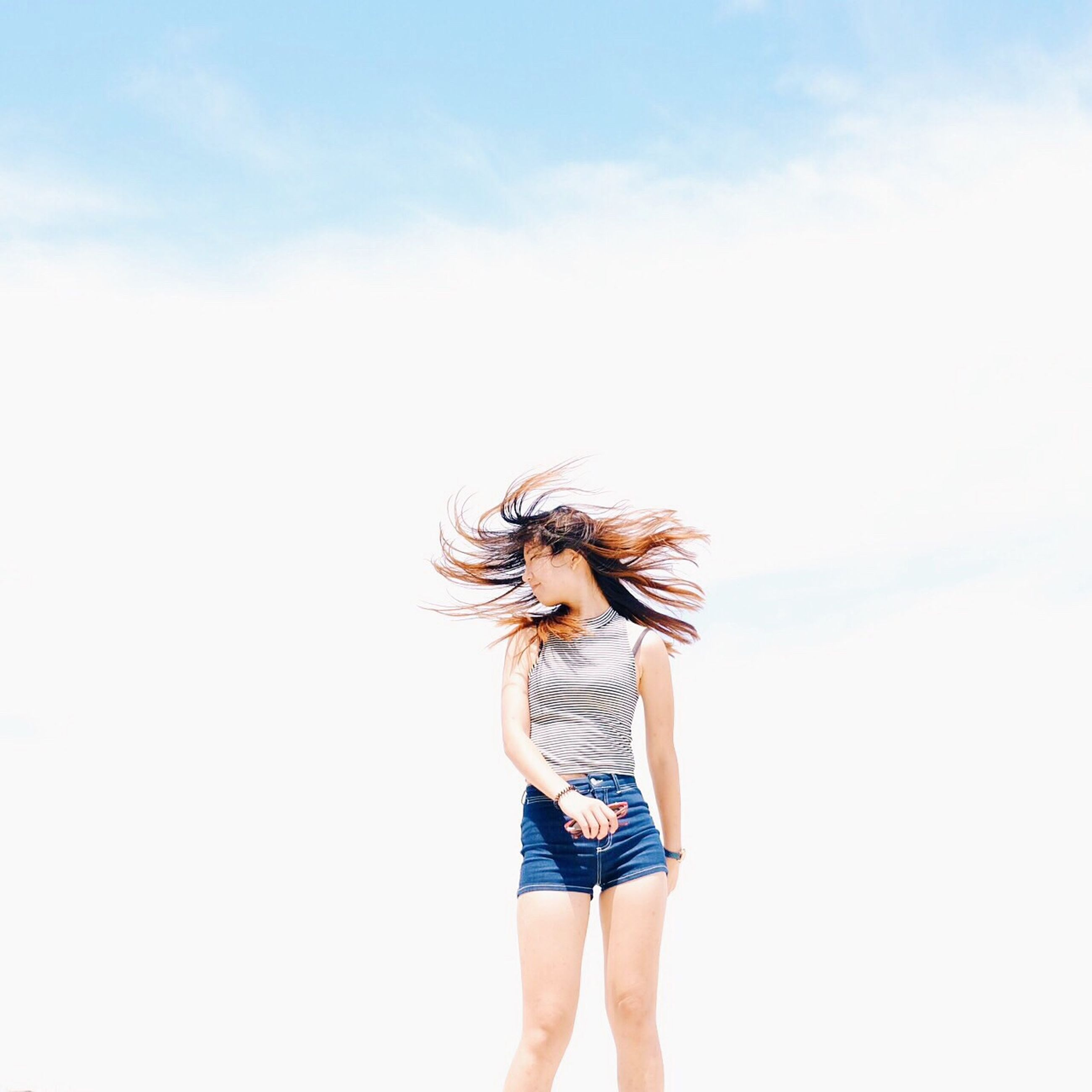 lifestyles, standing, leisure activity, young adult, copy space, young women, casual clothing, person, three quarter length, sky, front view, holding, low angle view, studio shot, arms raised, rear view, white background, long hair