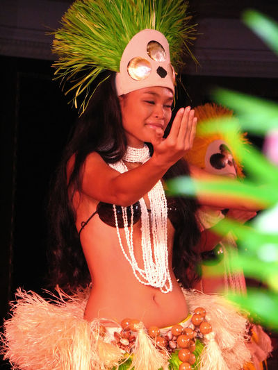 French Polynesian Touristic Cultural Show with local musicians and adult female dancers with family children- Island of Tahitti, French Polynesia Beautiful Polynesian Girl Beautiful Woman Beckoning Hand Celebration Coconut Bra Costume Feather  Happiness Headdress Indoors  Leisure Activity Lifestyles Long Pearl Necklace Night One Person People Portrait Real People Shell And Feathers Smiling Stage Costume Standing Young Adult Young Women