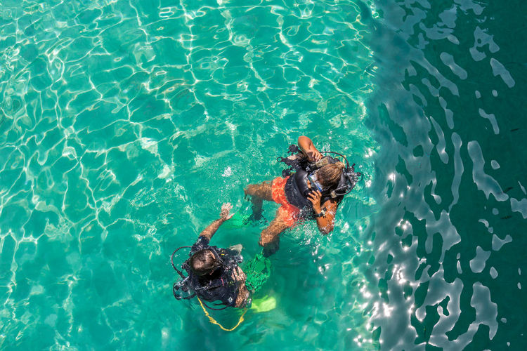 High angle view of friends scuba diving in sea