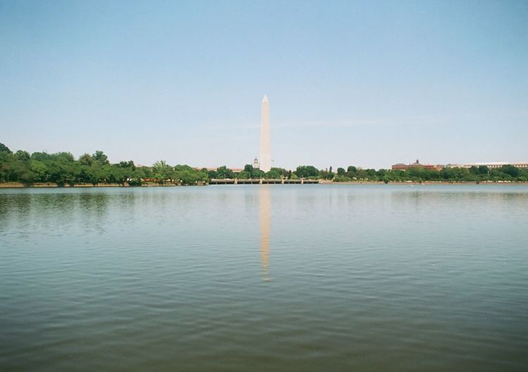 Washington monument by lake against clear sky