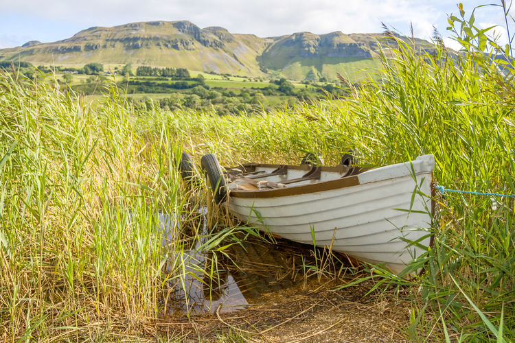 Boat in The Glencar lake in Ireland Plant Grass Land Growth Nature Green Color Nautical Vessel Day Field No People Tranquility Beauty In Nature Mode Of Transportation Landscape Transportation Scenics - Nature Outdoors Environment Tranquil Scene Non-urban Scene Rowboat Boat
