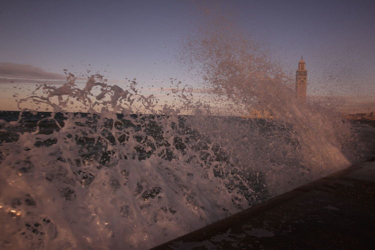 Waves flowing at sea with mosque hassan ii in background against sky
