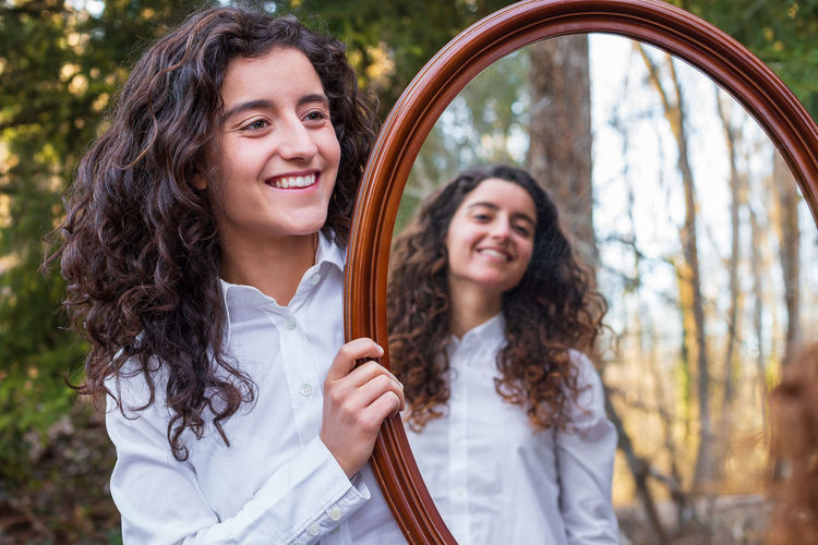Smiling woman holding mirror with sister reflection at forest