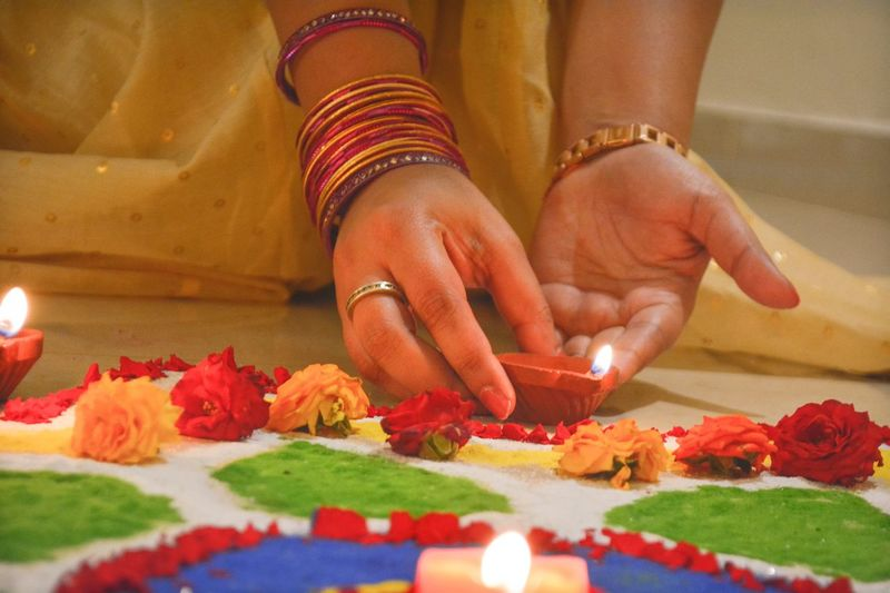Midsection of woman putting diya by rangoli during festival