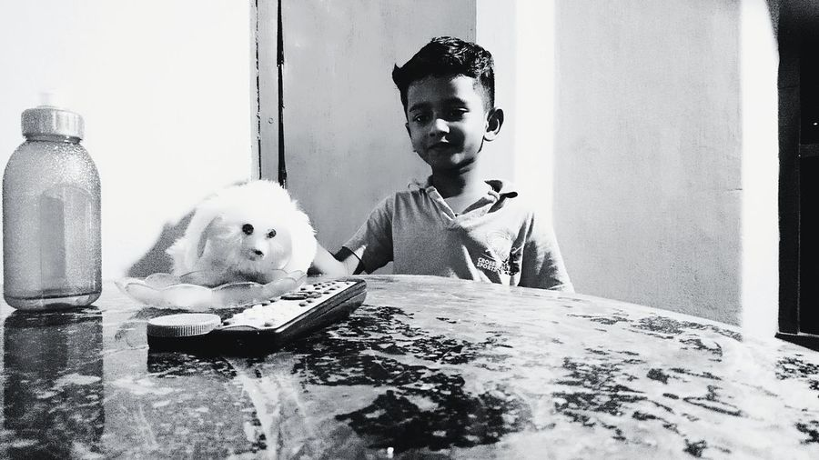 Boy with cat on table