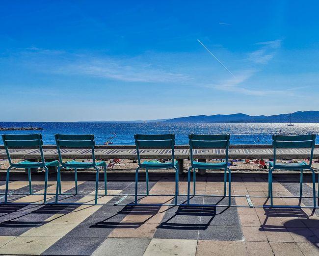 Empty chairs on beach against blue sky