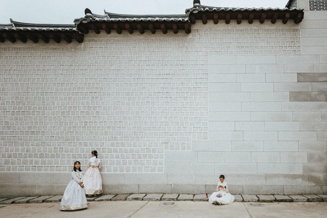COUPLE SITTING ON BRICK WALL