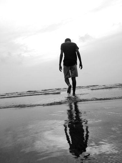 Rear view of man walking at beach