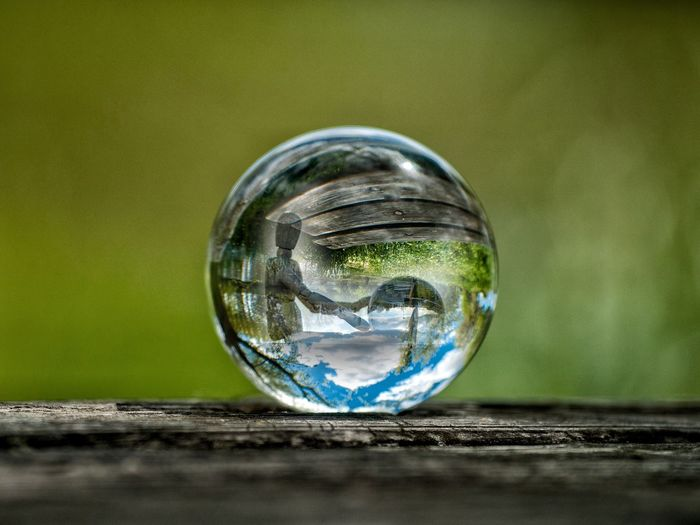 Close-up of crystal ball reflecting wooden figurine on table