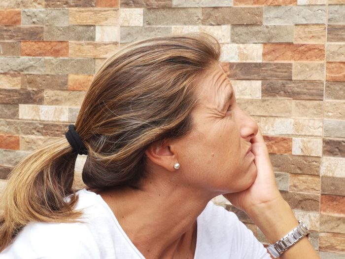 Side view of woman with hand on chin sitting against wall
