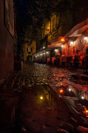 Illuminated Street By Buildings In City At Night During Rainy Season