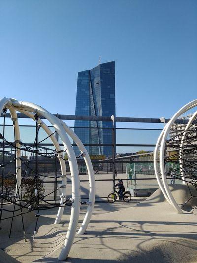 Ferris wheel by modern buildings against clear sky