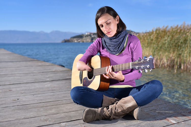 Woman playing guitar while sitting on pier by lake